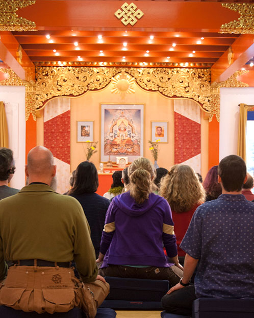 Meditators sit in Main Meditation Hall at Karme Choling Meditation Retreat Center